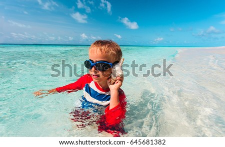 little boy listening to seashell on beach