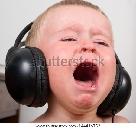 Little boy listening to the music in stereo headphones, crying and screaming - stock photo
