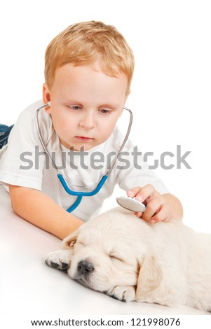 Little boy listens to retriever puppy through a stethoscope - stock photo