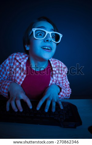 Little boy look to computer display. He like play and win video games. In blue light of display emotional kid play computer games online. - stock photo