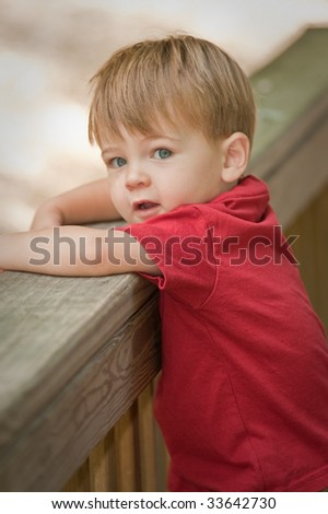 little boy looking a camera leaning over deck railing - stock photo