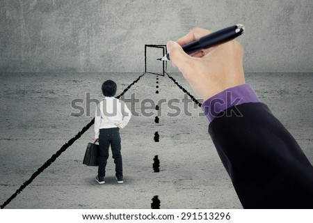 Little boy looking at a hand drawing a door at the end of a road - stock photo