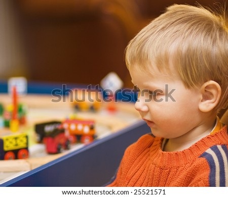 Little boy looking at his toys; selective focus