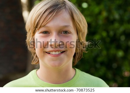 Little boy looking at the camera in the garden - stock photo