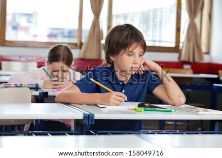 Little boy looking away while writing in book with classmate studying at classroom - stock photo