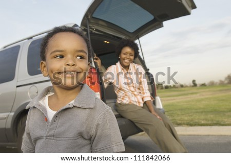 Little boy looking away with woman sitting in the boot of a car - stock photo