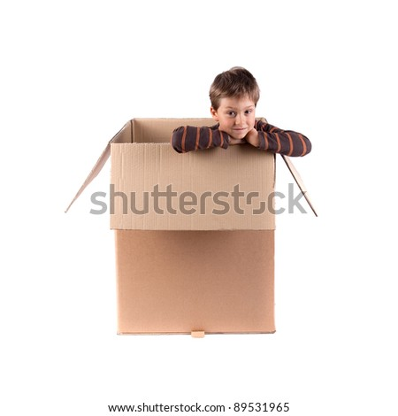 little boy looking from carton box