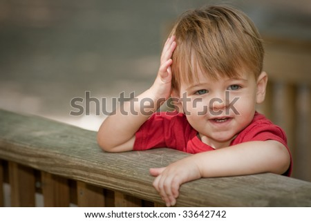 little boy looking happy with arms over deck railing and one on his head - stock photo