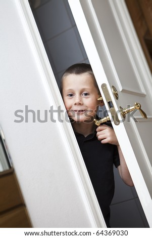 Little Boy looking out from the Closet - stock photo
