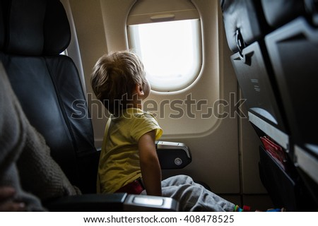 Little boy looking out of window in airplane