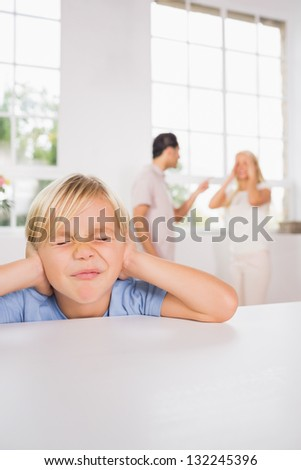 Little boy looking sad cause of parents fighting - stock photo