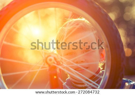 Little boy looking through a moving wheel on a background of the backlight. Vintage composition - stock photo