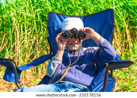 little boy looking through binoculars - stock photo
