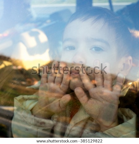 Little boy looking through window