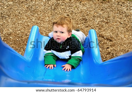 Little boy looks up from the bottom of the slide to face a new challenge/Facing a Challenge/Attempt to face the challenges that await - stock photo