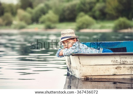 Little boy lying in the old boat on a pond at the summer evening - stock photo