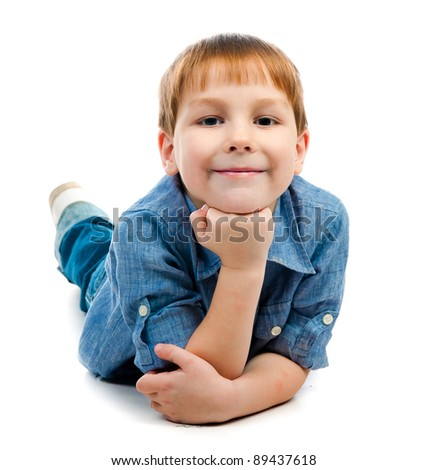 little boy lying on a white floor - stock photo