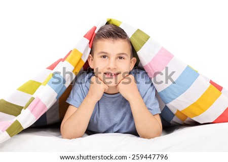 Little boy lying on bed covered with a blanket isolated on white background - stock photo