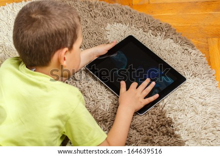 Little boy lying on floor and using digital tablet