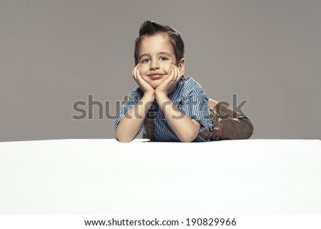 Little boy lying on the floor  - stock photo