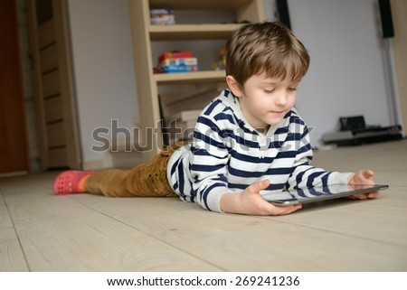 Little boy lying on the floor in the living room and uses his tablet. - stock photo