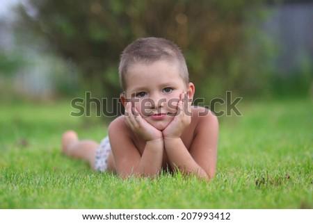 Little boy lying on the grass - stock photo