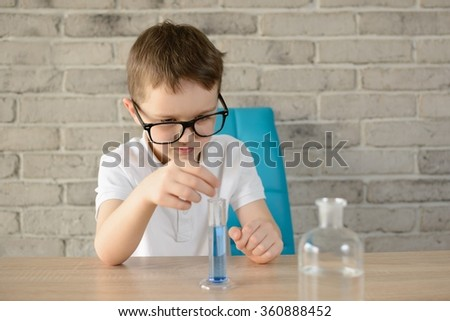 Little boy make an indoor chemical test with water and ph marker - stock photo