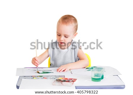 Little boy makes his first drawings in watercolor. Isolated on a white background. - stock photo