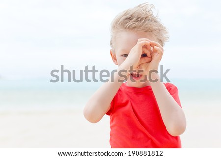 little boy making a spyglass with his hands, having fun during summer vacation - stock photo