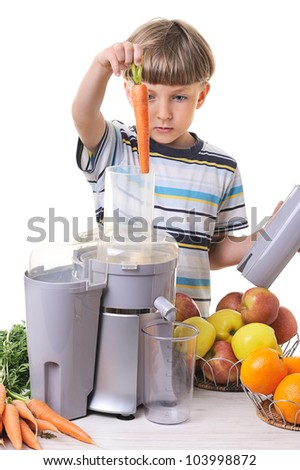 Little boy making fresh and healthy juice with a juice extractor