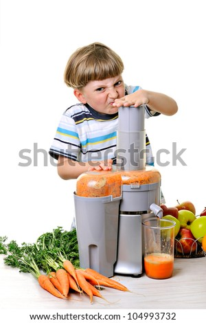 Little boy making fresh and healthy juice with a juice extractor - stock photo