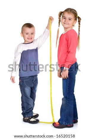 little boy measuring her sister's height - stock photo