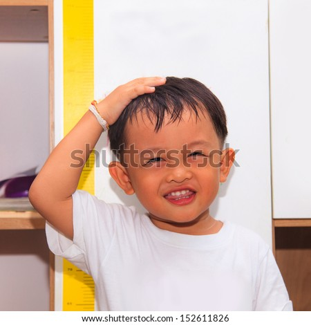 Little boy measuring his height  - stock photo