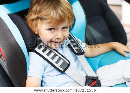 Little boy of 3 years sitting in safety car seat - stock photo