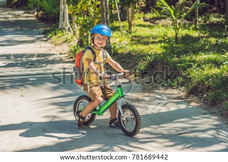 Little boy on a bicycle. Caught in motion, on a driveway motion blurred. Preschool child's first day on the bike. The joy of movement. Little athlete learns to keep balance while riding a bicycle.