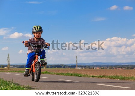 Little boy on a bicycle for the first time. Small child learns to ride a bike. Safe Driving preschool child with a helmet.  - stock photo