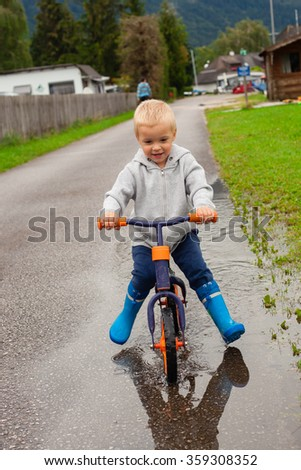 Little boy on a bicycle passes through puddles.
