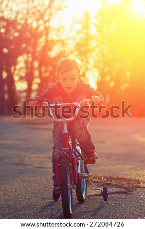 Little boy on a bicycle racing towards his goal against the background of the backlight. Vintage composition - stock photo