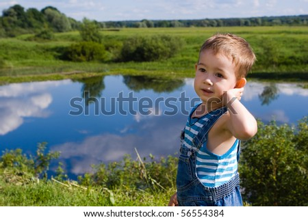 Little boy on a  summer lake background - stock photo