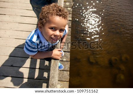 Little boy on a wooden bridge looking curious on a hot summer day - stock photo