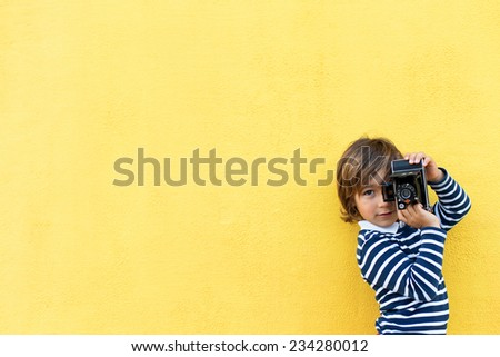 little boy on a yellow wall wearing a stripes sweater taking a photo using a vintage camera - stock photo