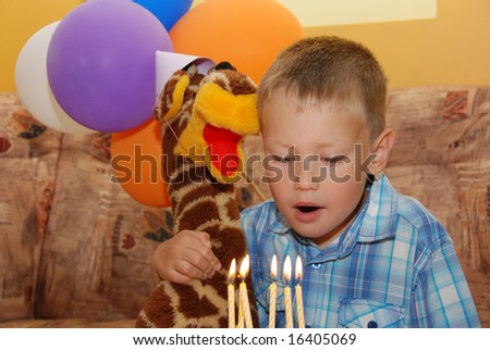 Little boy on birthday party with his favorite toy - stock photo