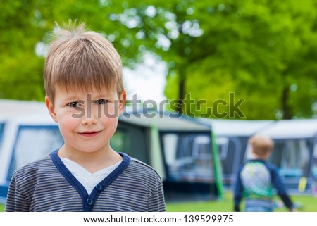 Little boy on camping site with caravan tent in background