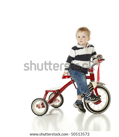 Little Boy on His Tricycle Looking Uncertain - stock photo