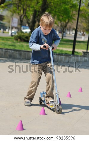 Little boy on scooter - stock photo