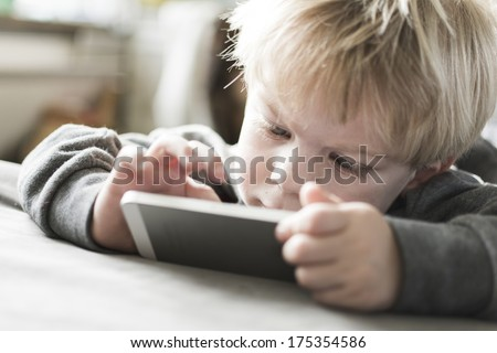 Little boy on smartphone - stock photo