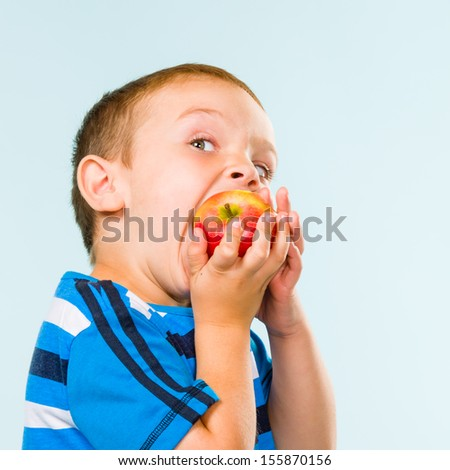 Little boy on striped t-shirt eating apple, studio shot and light blue background - stock photo