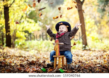 little boy on the wooden rocking horse in the autumn forest - stock photo