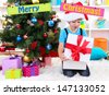Little boy open his gifts near Christmas tree - stock photo