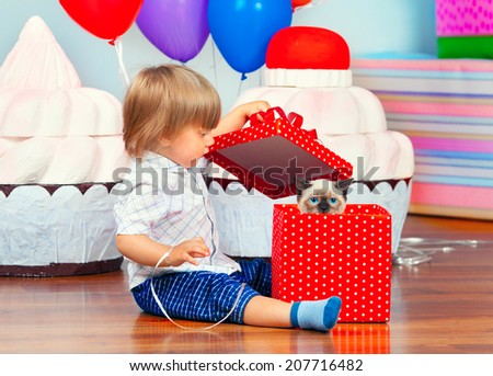 Little boy opening his first birthday present - stock photo